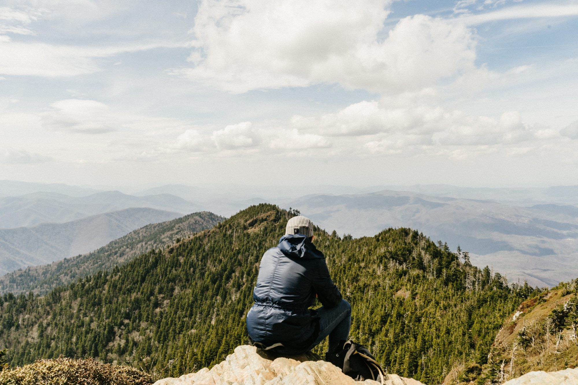 man sitting on top of a hill overlooking green mountains