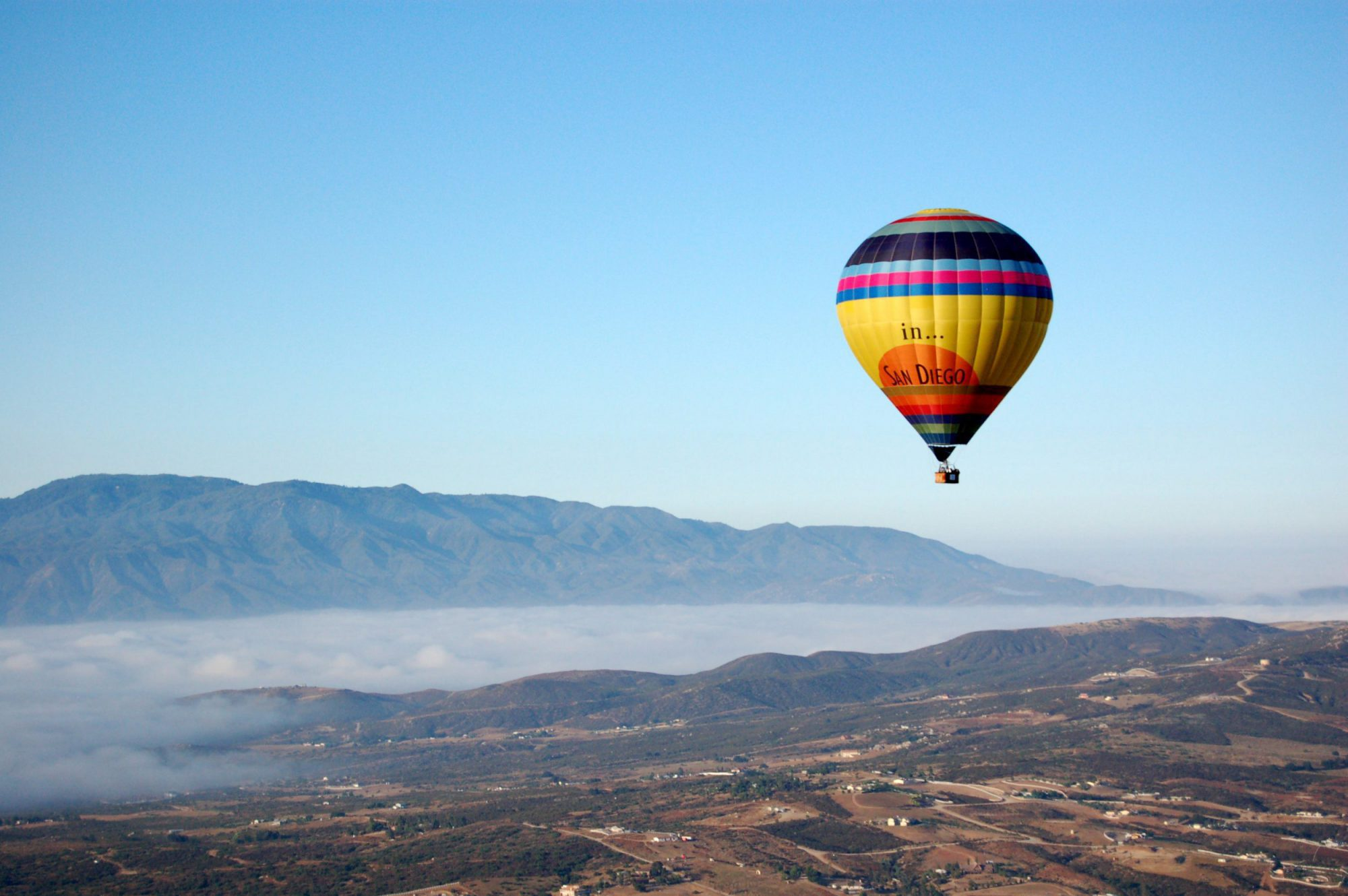 hot air balloon floating across the land with mountains in the background