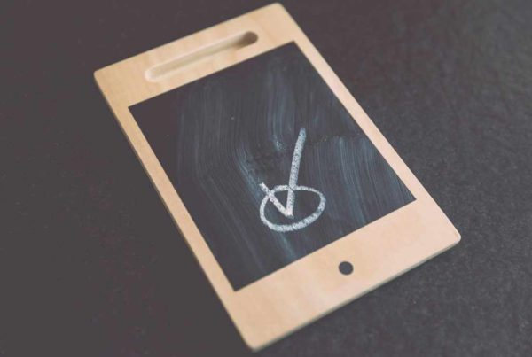 mobile tablet with a tick in a circle drawn in chalk